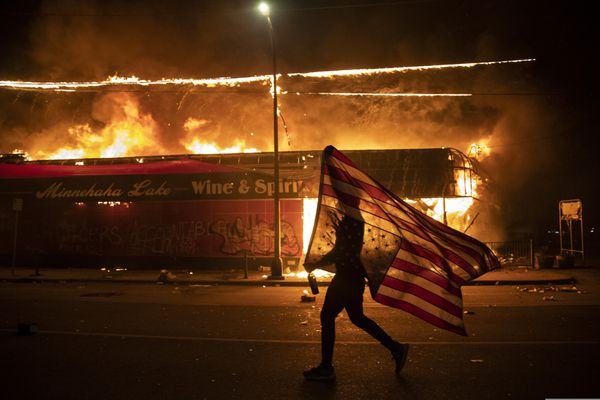 A protester carries a U.S. flag upside down, a sign of distress, next to a burning building, May 28, 2020, in Minneapolis. Protests over the death of George Floyd, a black man who died in police custody, broke out in Minneapolis for a third straight night. The image was part of a series of photographs by The Associated Press that won the 2021 Pulitzer Prize for breaking news photography. (AP Photo/Julio Cortez)