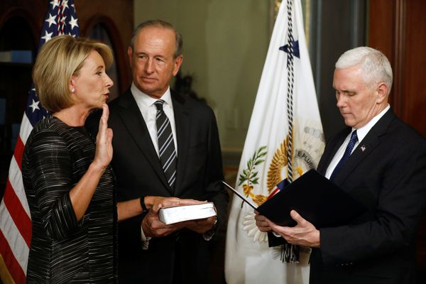 U.S. Vice President Mike Pence (R) swears in Education Secretary Betsy DeVos (L), joined by her husband Dick DeVos (2nd L), at the Eisenhower Executive Office Building at the White House in Washington, U.S. February 7, 2017. REUTERS/Jonathan Ernst