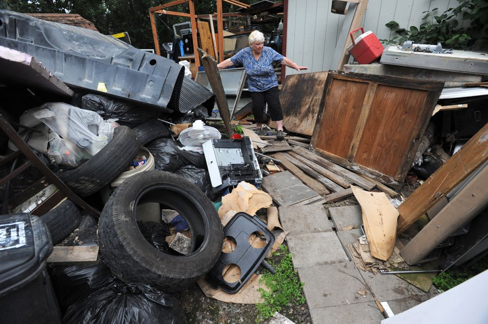 Owner Gail Somerville negotiates the path in the backyard of her junk-filled property. (Erik Hill / Alaska Dispatch News)
