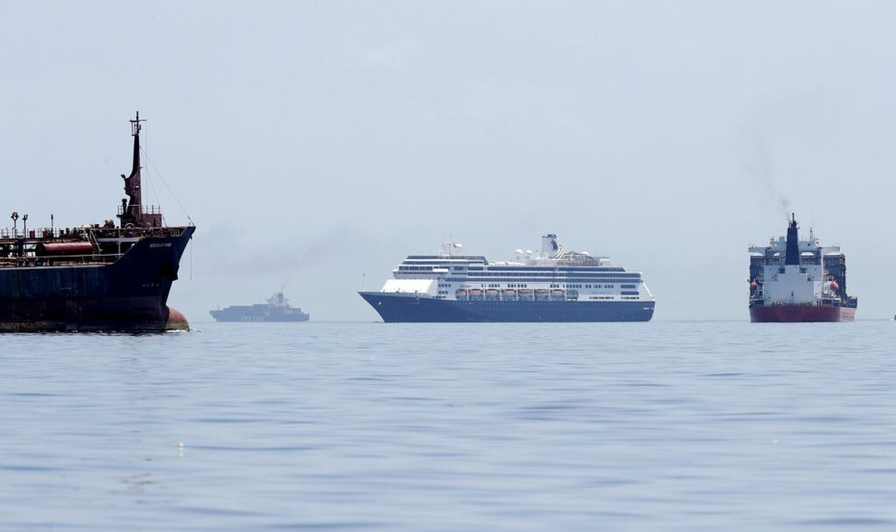 The Zaandam cruise ship, center, carrying dozens of guests with flu-like symptoms, arrives to the bay of Panama City, seen from Isla de Taboga, Panama, Friday, March 27, 2020, amid the worldwide spread of the new coronavirus. (AP Photo/Arnulfo Franco)