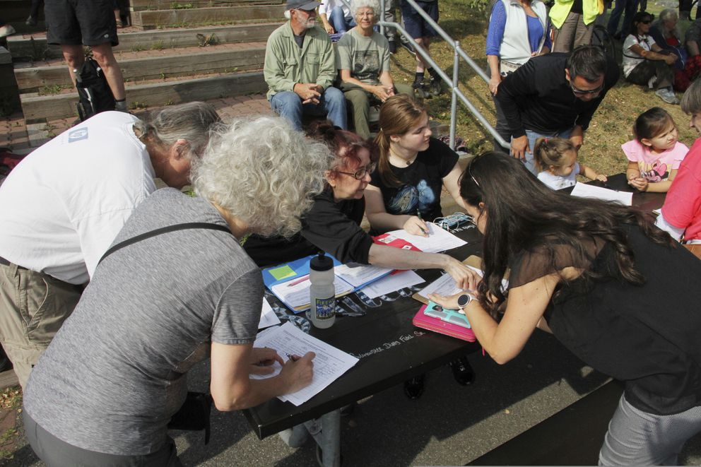 Residents gathered Thursday, Aug. 1, 2019, in Anchorage, Alaska, to sign petitions to recall Alaska Gov. Mike Dunleavy. Dunleavy angered many in the last few weeks with budget vetoes of more than $400 million. (AP Photo/Mark Thiessen)