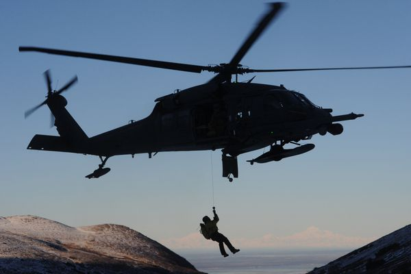 Senior Master Sgt. Eric Taylor, a pararescueman with the 212th Rescue Squadron, is hoisted up to a hovering HH-60G Pave Hawk helicopter from the 210th Rescue Squadron during an extraction training mission in the Chugach Mountains east of Anchorage on Wednesday, Jan. 21, 2015.