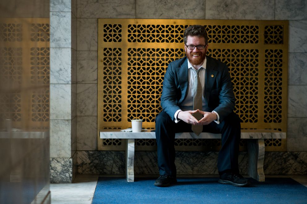 Rep. Justin Parish, D-Juneau, sits in the entry to the state Capitol. (Marc Lester / Alaska Dispatch News)