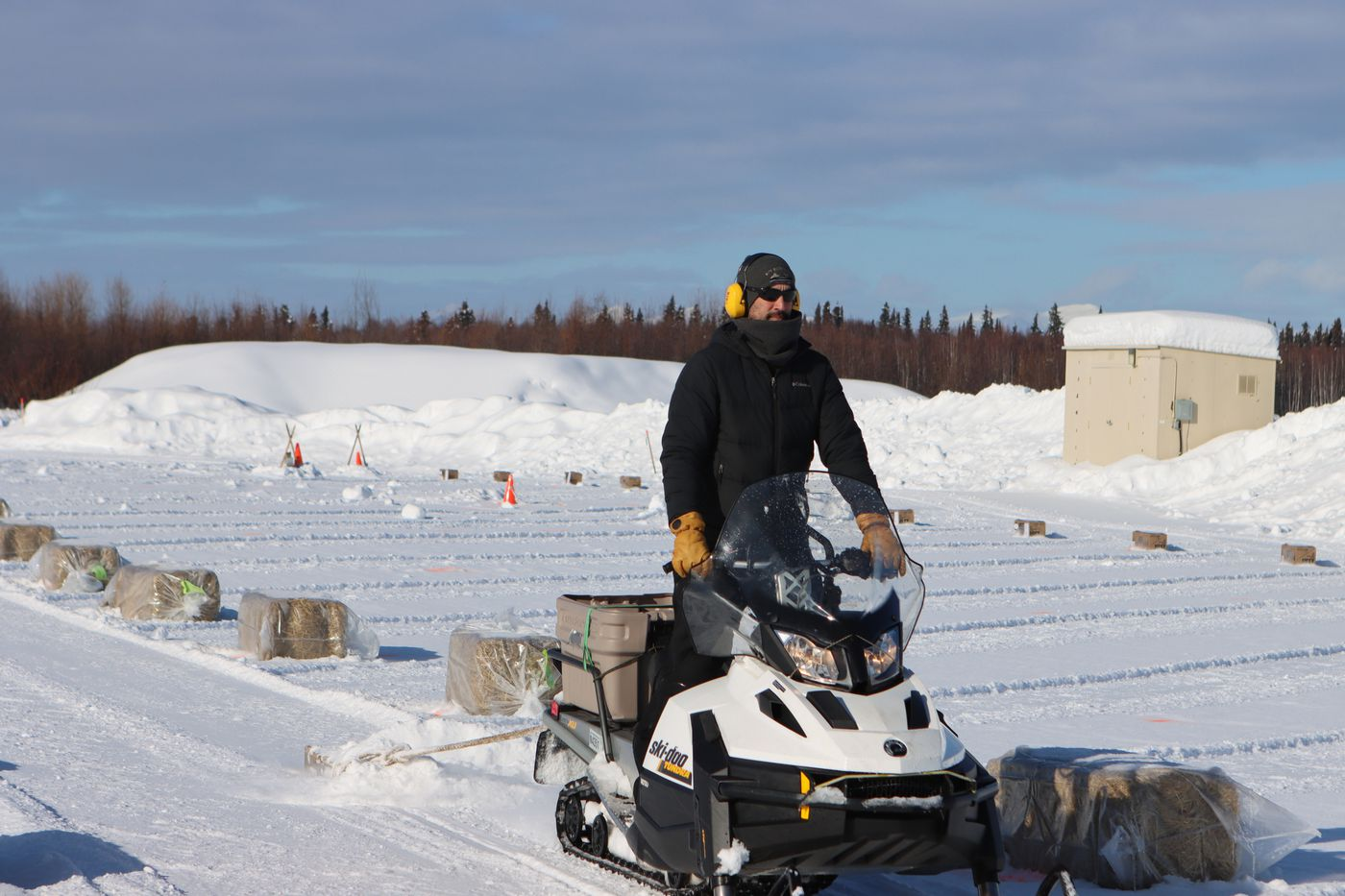 A snowmachiner drags a pallet to smooth out snow lanes in the new dog lot which has been set up in McGrath to accommodate Covid precautions. It is a tidy and well laid out staging area, complete with parking lanes for the Iditarod teams. (Zachariah Hughes/for ADN)