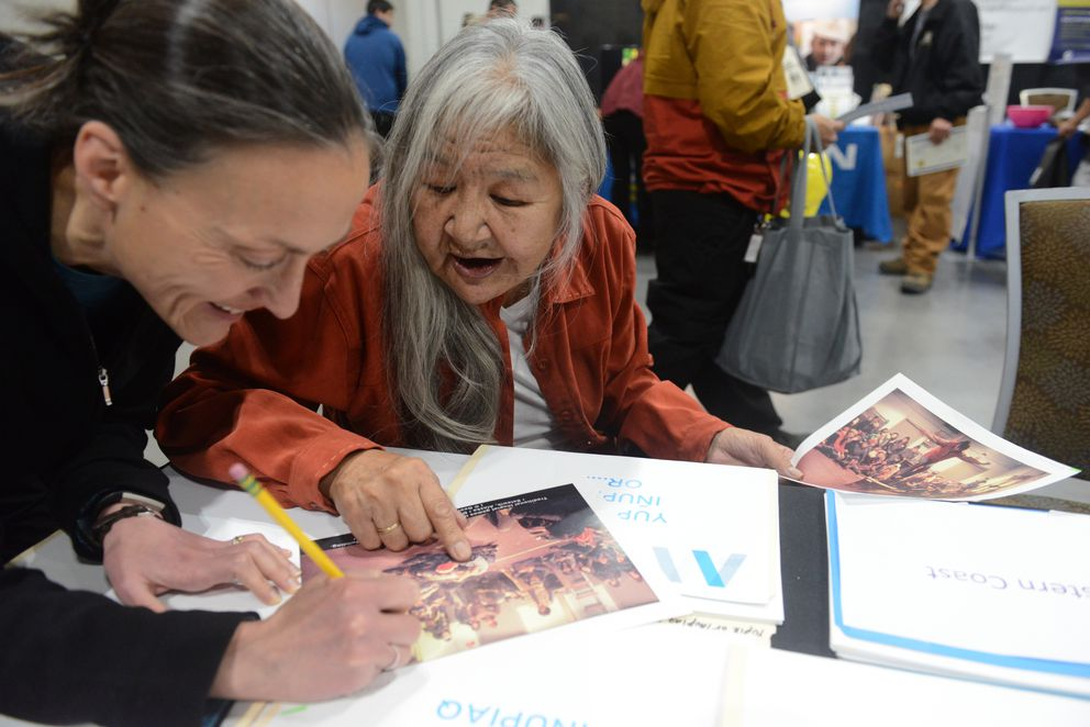 Anchorage Museum archivist Sara Piasecki writes down names provided by Mary Foster for a photograph from Selawik, AK. (Bob Hallinen / ADN)