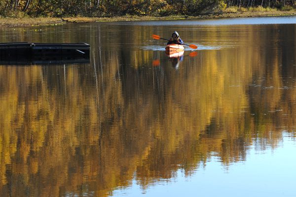 Fall colors reflect on the glassy surface of Little Campbell Lake as Laura Walker paddled a kayak on a sunny Thursday afternoon, Oct. 3, 2019. (Bill Roth / ADN)