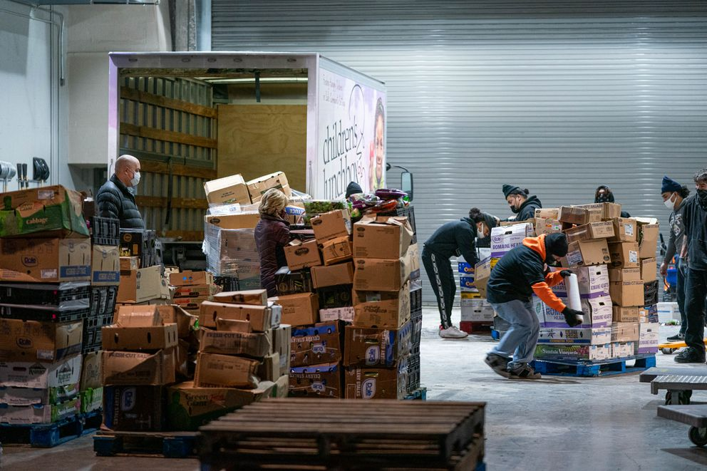 Bean's Cafe staff sort and load fresh produce salvaged from an overturned truck on Saturday, Dec. 26, 2020 at the Dena'ina Civic and Convention Center in Anchorage. (Loren Holmes / ADN)