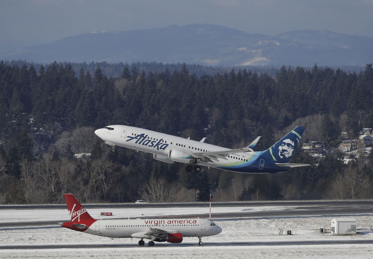 An Alaska Airlines plane takes off above a taxiing Virgin America plane, Tuesday, Feb. 5, 2019, at Seattle-Tacoma International Airport in Seattle. (AP Photo/Ted S. Warren)