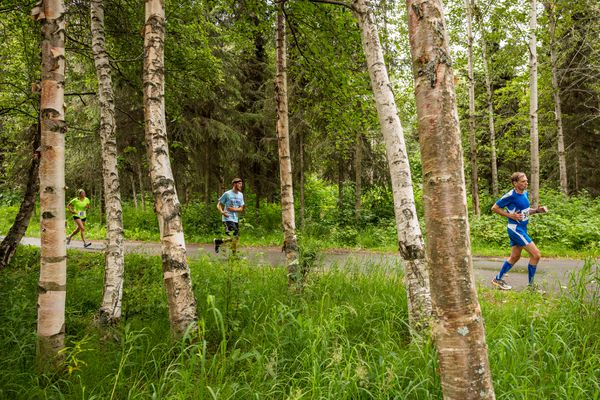 Tom Pickerel of Genoa, Ohio, right, leads a group of runners through the Chester Creek greenbelt during the Alaska Men's Run on Saturday, July 19, 2014.
