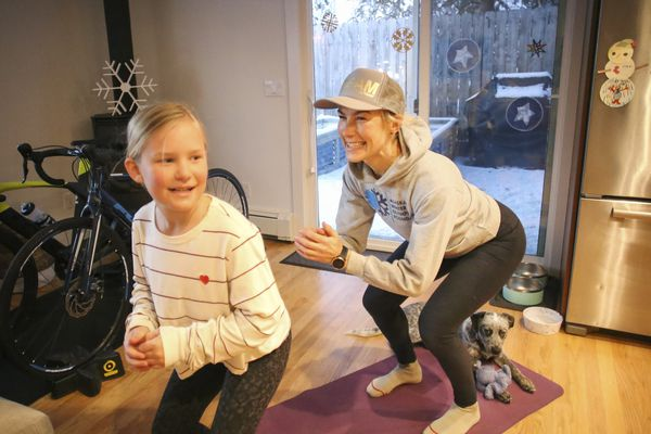 Rosey Fletcher and her daughter, Olga, 8, listen to music as they complete 200 squats as part of Fletcher's 200-squats-a-day challenge at their home in Anchorage on Nov. 16, 2020. (Emily Mesner / ADN)
