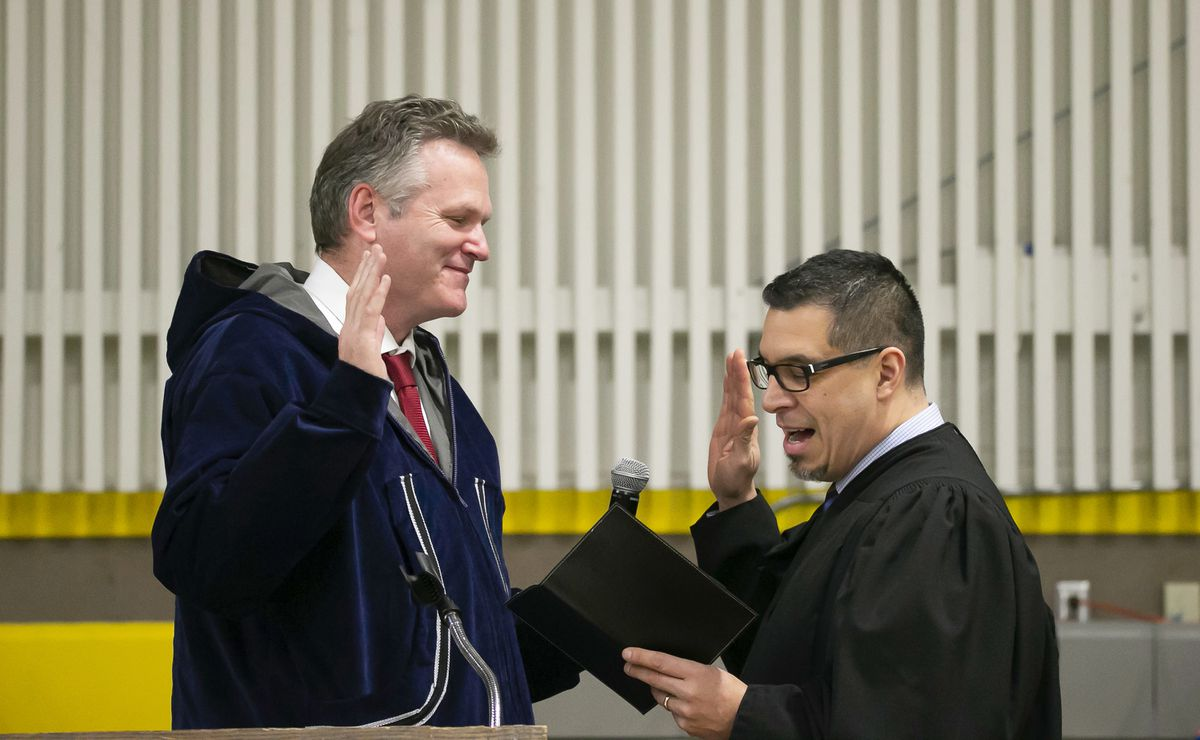Mike Dunleavy, left, is sworn into office as Alaska's governor by Superior Court Judge Paul Roetman in Kotzebue on Monday. (Stanley Wright/Alaska Governor's Office via AP)