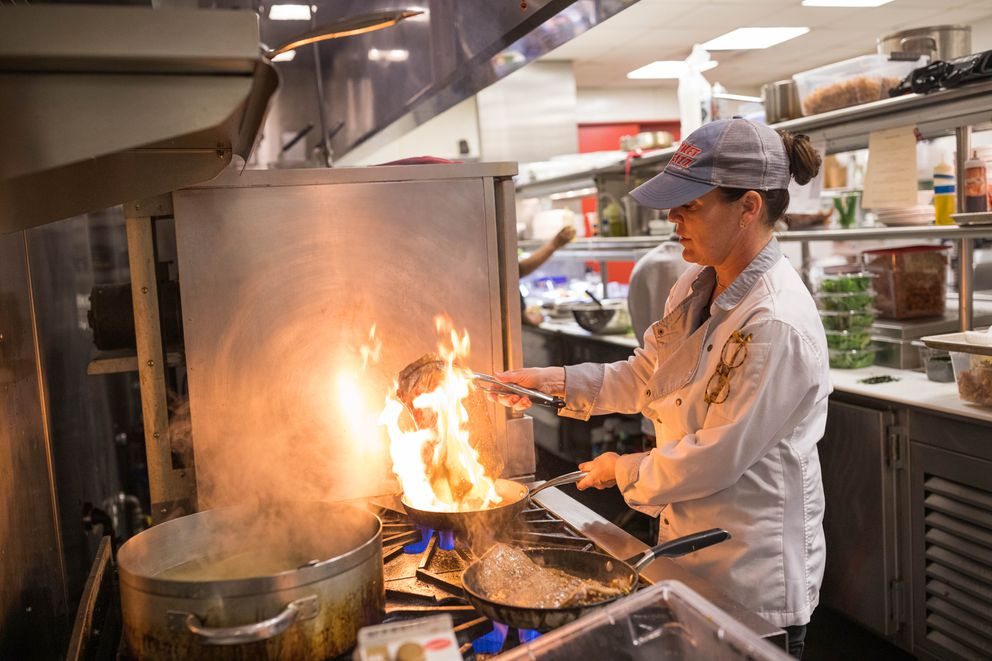 Chef Laura Cole prepares flank steak at Muse on Tuesday, July 16, 2019. (Loren Holmes / ADN)