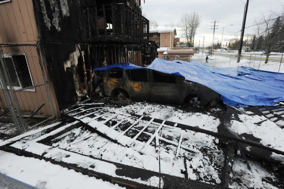 Charred vehicles on the west end of the Royal Suite Apartments are covered by a tarp on Thursday, Feb. 16, 2017. (Bill Roth / Alaska Dispatch News)
