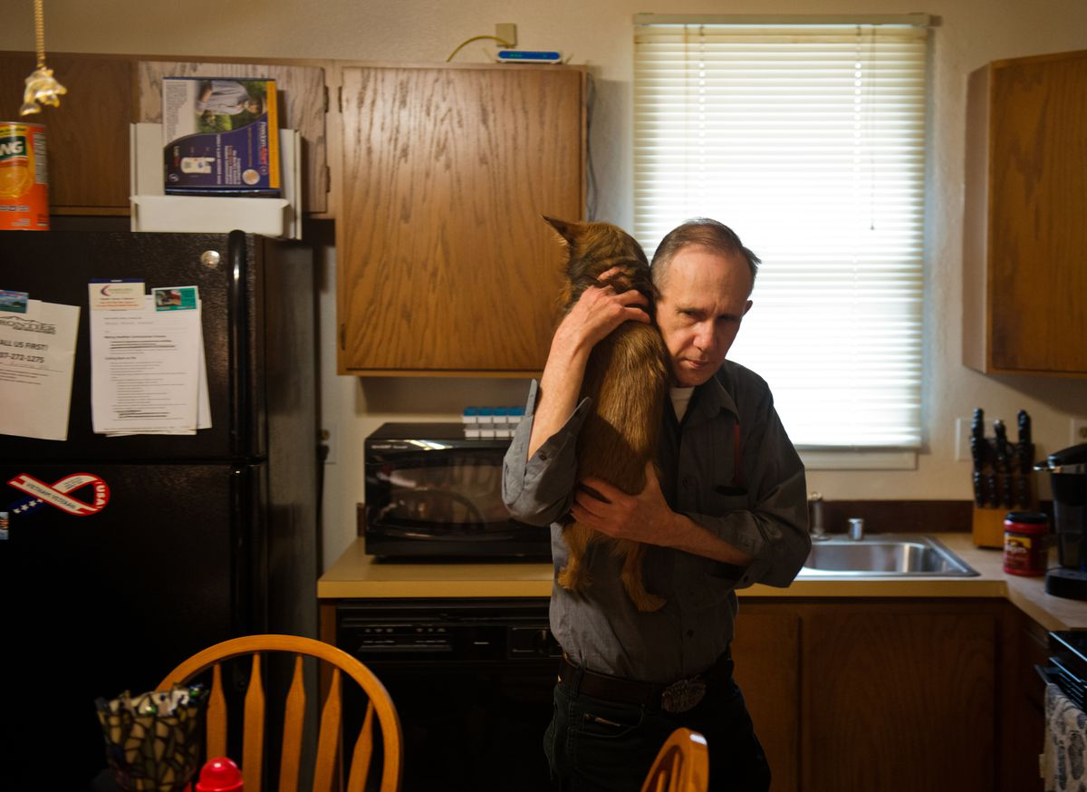 Mike Gervell carries Mikey in his Anchorage home on Tuesday, April 14, 2015. Gervell was paired with the dog by Midnight Sun Service Dogs earlier this year.