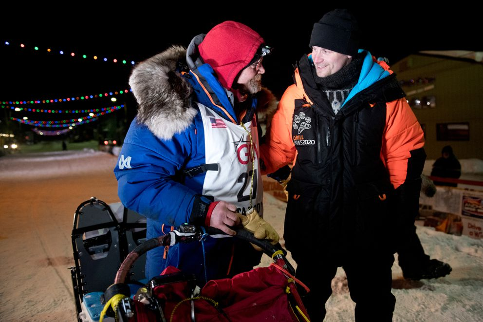 Mitch Seavey, left, is greeted by son Dallas Seavey at the finish line in Nome after his second-place finish in this year's Iditarod. (Marc Lester / ADN)