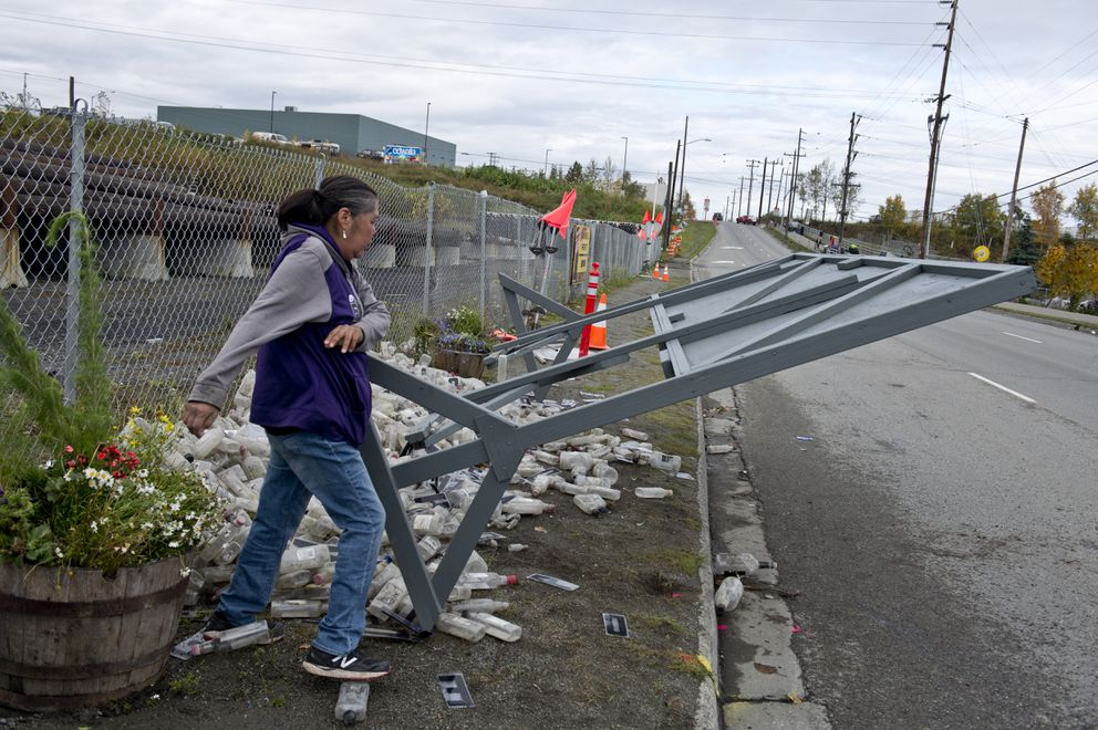 A woman knocks over a sign, erected by Ron Alleva, across from the Brother Francis Shelter. (Marc Lester / Alaska Dispatch News)