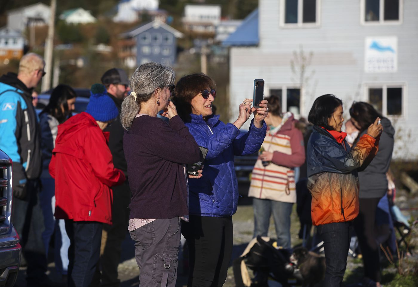 People gather on a lot across from the Cordova boat harbor and record members of the fleet as they return from the first commercial opener of the season on Monday, May 17, 2021. (Emily Mesner / ADN)