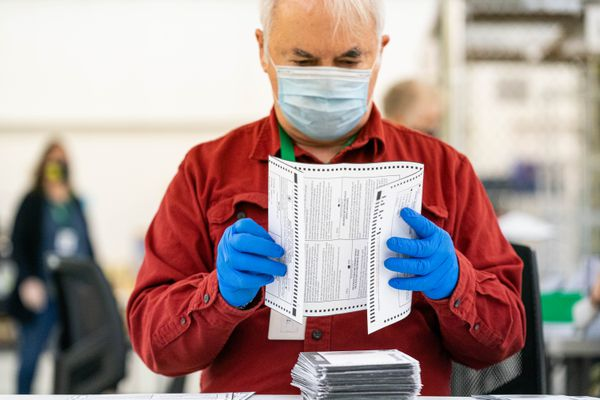 Election worker Marvin Cox unfolds a ballot so it can be scanned on Wednesday, April 7, 2021 at the Municipality of Anchorage election center. The municipality is continuing to count ballots a day after election day. (Loren Holmes / ADN)