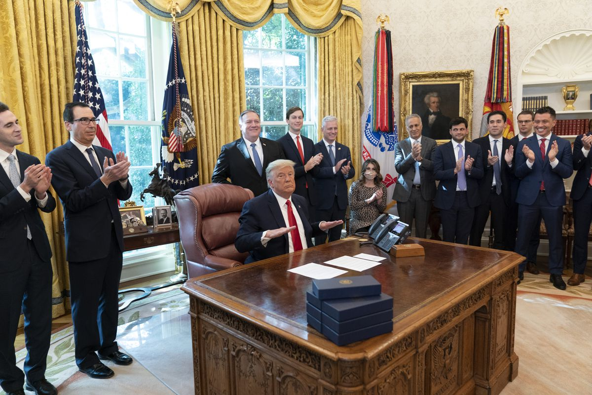 President Donald Trump reacts after hanging up a phone call with the leaders of Sudan and Israel, as Treasury Secretary Steven Mnuchin, second from left, Secretary of State Mike Pompeo, White House senior adviser Jared Kushner, National Security Adviser Robert O'Brien, and others applaud in the Oval Office of the White House, Friday, Oct. 23, 2020, in Washington. (AP Photo/Alex Brandon)