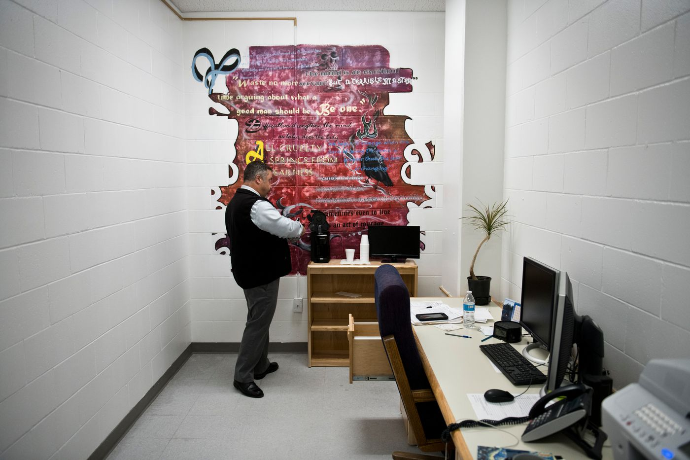 "Spring Creek Correctional Center superintendent Bill Lapinskas makes coffee after his early-morning arrival to work on Sept. 27. A mural, painted on his office wall by prisoners, includes sayings he had collected and sometimes shared with others, such as ""All cruelty springs from weakness."" (Marc Lester / ADN)"