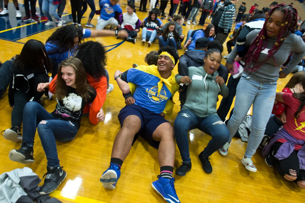 Bartlett senior Herman Grey, center, participates in an activity where students stood back-to-back and tried to support each other as they sat down on the gym floor. About 80 junior and senior student mentors led activities for more than 400 incoming freshman at Bartlett High School on August 20. The program, called Link Crew, was designed to give newcomers the chance to make connections, get familiar and receive encouragement before classes begin. (Marc Lester / ADN)