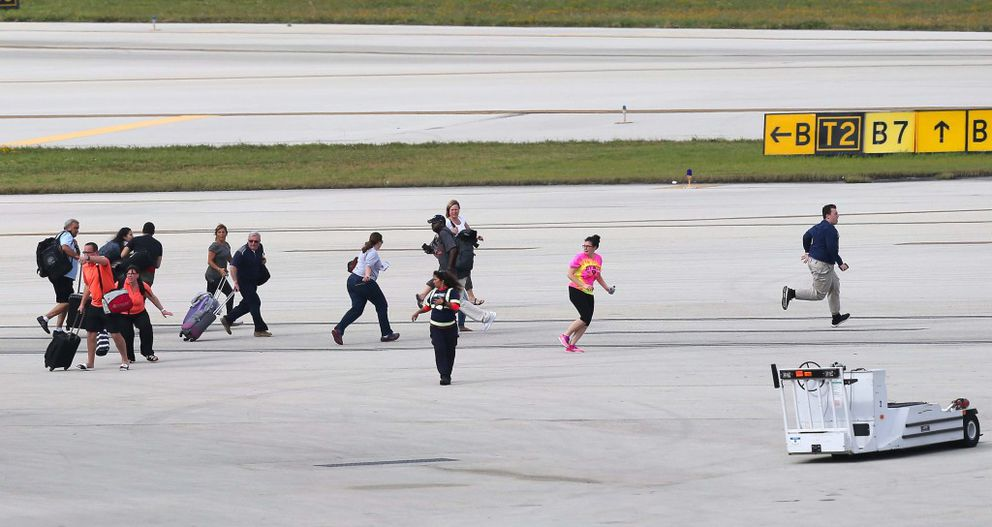 People run for cover on the tarmac after a lone suspect opened fire at the Ft. Lauderdale-Hollywood International Airport on Friday, Jan. 6, 2017, in Florida. (David Santiago/El Nuevo Herald/TNS)