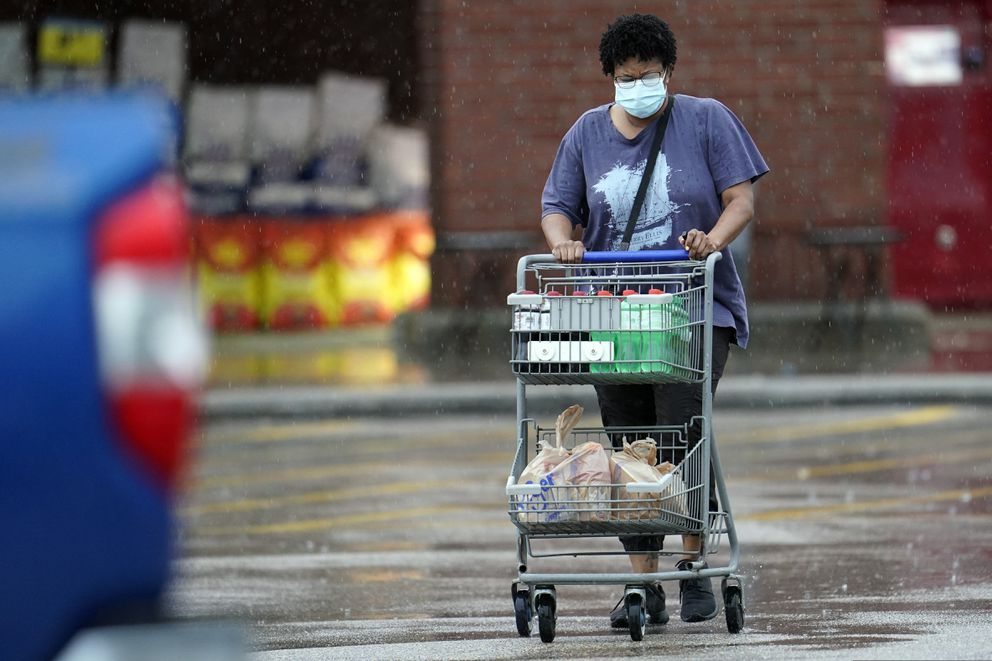 A shopper wears a mask as she pushes her grocery cart in the rain Thursday, June 25, 2020, in Houston. (AP Photo/David J. Phillip)