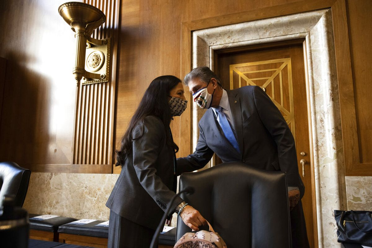 Sen. Joe Manchin, D-W.Va., talks with Rep. Deb Haaland, D-N.M., before the start of the Senate Committee on Energy and Natural Resources hearing on her nomination to be Interior Secretary, Tuesday, Feb. 23, 2021 on Capitol Hill in Washington. (Graeme Jennings/Pool via AP)
