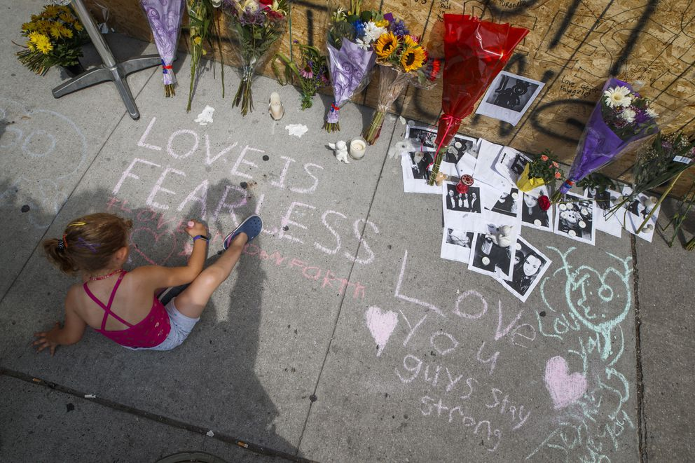 A young girl writes a message on the sidewalk at a site remembering the victims of a Sunday evening shooting on Danforth Avenue, in Toronto on Monday, July 24, 2018. (Mark Blinch/The Canadian Press via AP)