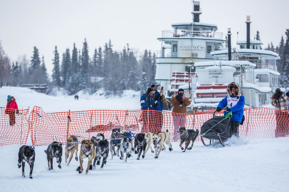Four-time champion Martin Buser mushes past the Riverboat Discovery on the Chena river in Fairbanks in 2015. (Loren Holmes / Alaska Dispatch News)