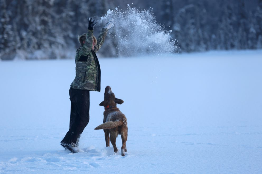 Christine Cunningham throws snow in the air while a mesmerized Jack watches. (Photo by Steve Meyer)