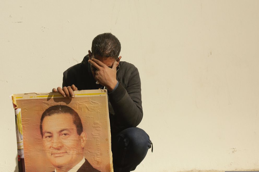 FILE - In this Feb. 26, 2020, file photo, a supporter holds a photo of Egypt's ousted autocratic President Hosni Mubarak as he weeps outside the gate of the mosque ahead of his funeral in New Cairo, Egypt. Mubarak, 91, the Egyptian leader who was the autocratic face of stability in the Middle East for nearly 30 years before being forced from power in an Arab Spring uprising, died Feb. 25. (AP Photo/Maya Alleruzzo, File)