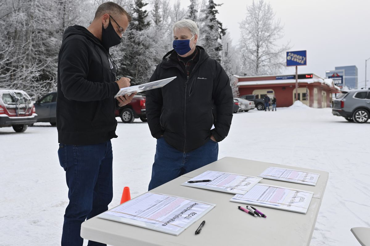 Josh Holland, left, signs a petition to recall Anchorage Assembly member Felix Rivera on January 4, 2021. Political consultant Scott Kohlhaas is at right. (Marc Lester / ADN)