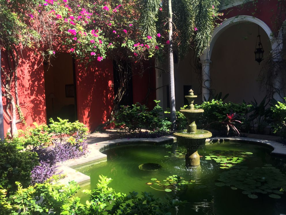 A secret garden inside Villa Merida, a hotel in Merida's central historic district in Mexico. Look closely on the right to see one of several hammocks, which are the preferred sleeping accommodations during the hot summer months. (Scott McMurren)