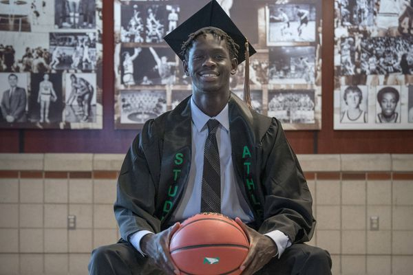 Bentiu Panoam of Anchorage wears his cap and gown after becoming the first person on his family to graduate from college in May 2021. Panoam, who attended graduating the University of North Dakota on a basketball scholarship, is the son of Sudanese refugees and one of 10 children in his family. (Photo by Crystal Saddler)