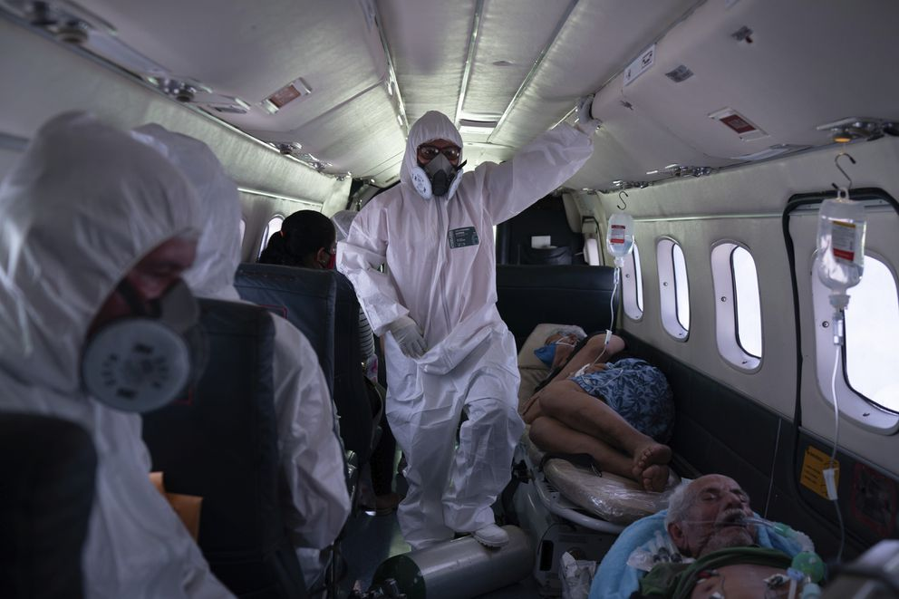 Nurse Janete Vieira, center, and Doctor Daniel Siqueira monitor COVID-19 patients onboard an aircraft as they are transferred from Santo Antônio do Içá to a hospital in Manaus, Brazil, Tuesday, May 19, 2020. The virus has spread upriver from Manaus, creeping into remote riverside towns and indigenous territories to infect indigenous tribes. (AP Photo/Felipe Dana)
