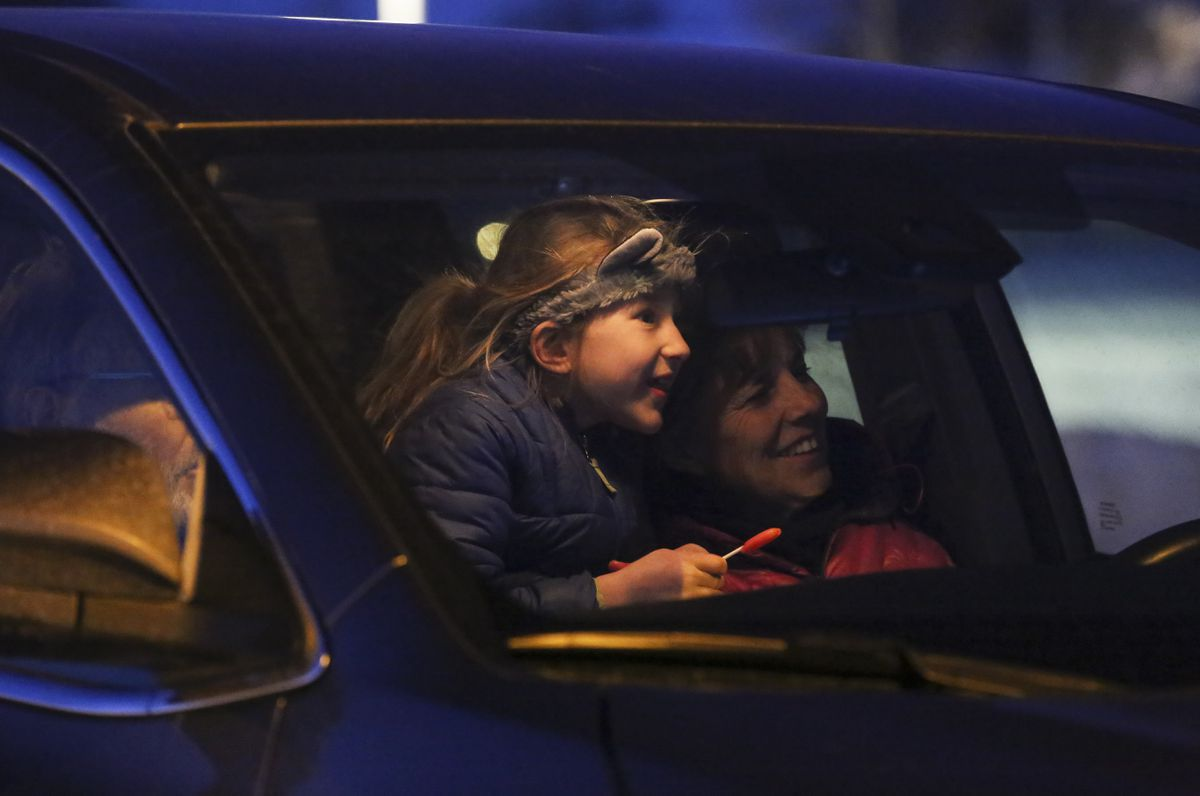 Story McDonald, 7, sits between her grandparents, Willy and Rose Van Hemert, while they watch a projection of ASD's Student Art Show that is being projected onto the outside of the East Anchorage High School building on March 12, 2021. (Emily Mesner / ADN)