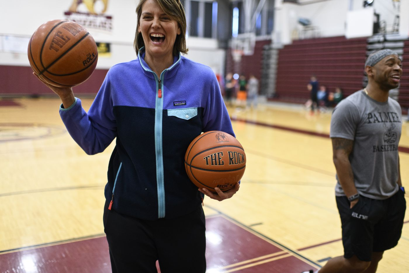 Amy Fogle laughs with her former players. Members of the 2001 Kodiak High School boys varsity basketball team gathered for a pickup game in Anchorage on April 25, 2019. Their high school state championship game was inducted into the Alaska Sports Hall of Fame this year. (Marc Lester / ADN)