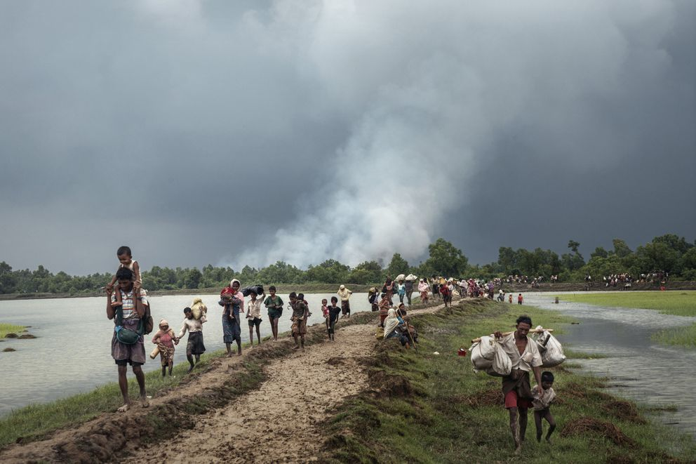 Villages burn in the distance as Rohingya refugees walk near the Naf River separating Myanmar and Bangladesh, near Palong Khali, Bangladesh, Sept. 4, 2017.  (Adam Dean/The New York Times)