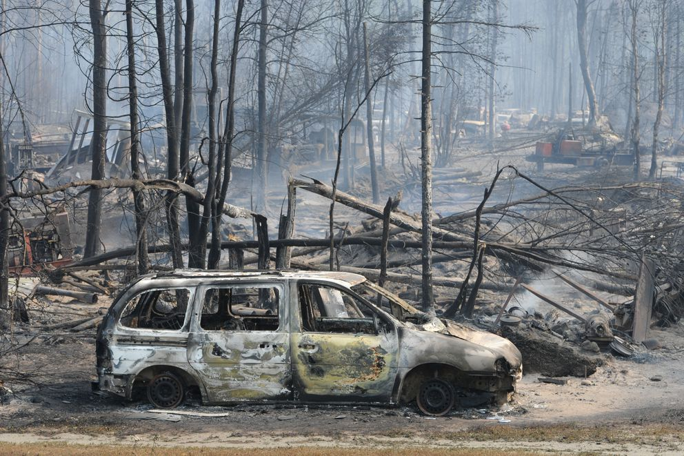 Smoke rises from vehicles and structures at Mile 86 of the Parks Highway on Monday, Aug. 19, 2019, that were damaged during the fast moving wildfire near Caswell. (Bill Roth / ADN)