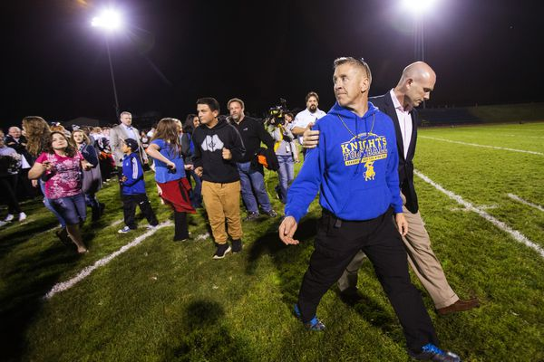Bremerton High School assistant football coach Joe Kennedy walks off the field with his lawyer after praying at the 50-yard line after a football game last week.