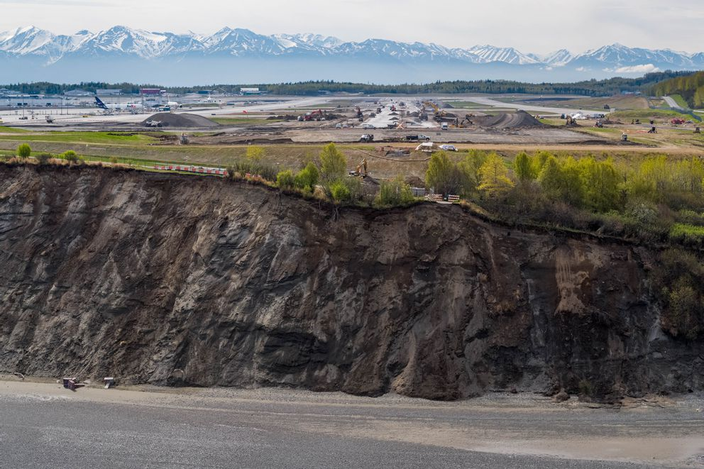 The eroding bluff is seen in front of the north-south runway at Ted Stevens Anchorage International Airport on Tuesday, May 14, 2019. The bluff has been eroding for many years and is encroaching on the popular Tony Knowles Coastal Trail and nearby road. The Ted Stevens Anchorage International Airport, behind, is expanding the runway and adding additional navigation lights. (Loren Holmes / ADN)
