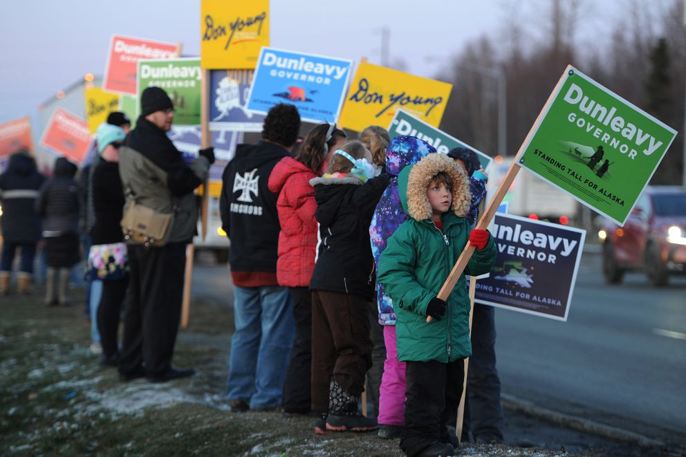 Cyprian Thompson, 7, waves a Dunleavy for Governor campaign sign along the Seward Highway near Northern Lights Boulevard on Monday, Nov. 5, 2018. (Bill Roth / ADN)