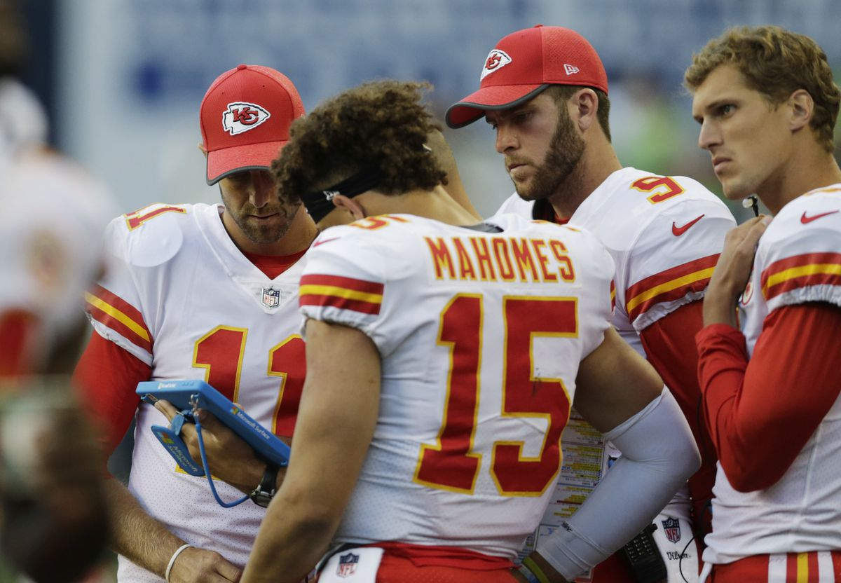 Kansas City Chiefs quarterbacks (from left) Alex Smith, Patrick Mahomes(15), Tyler Bray (9) and Joel Stave, right, view a tablet computer on the sideline during the second half of an NFL football preseason game against the Seattle Seahawks, Friday, Aug. 25, 2017, in Seattle. (AP Photo/John Froschauer)