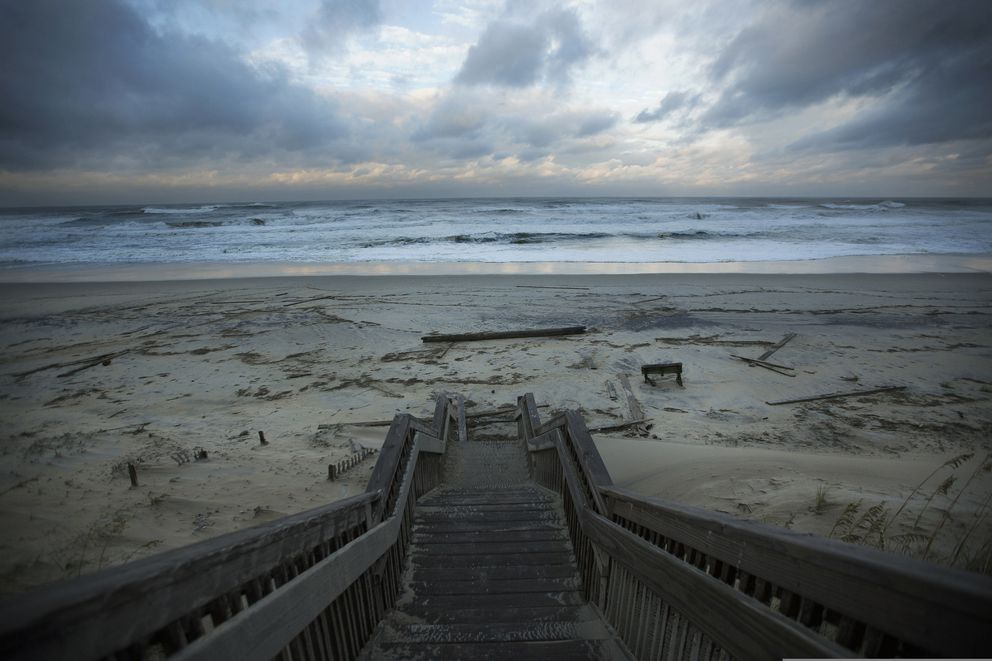 Wood debris is left scattered across the Nags Head beach in the Outer Banks, N.C., as the sunsets, Friday, Sept 6, 2019. (L. Todd Spencer/The Virginian-Pilot via AP)