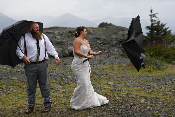 Robert Kurek and Kennedy Budd encounter wind while they stop for pictures and video at Beluga Point shortly before they planned to get married at Bird Point on Turnagain Arm on August 26, 2020. The couple, from Ottawa Lake, Michigan, had planned to marry in the Virgin Islands in spring, but changed their plans because of the pandemic. They decided to elope instead and get married six years to day since they first met. Though they dealt with rain and wind during some of their photo session, weather improved and some sun broke through before their ceremony. (Marc Lester / ADN)