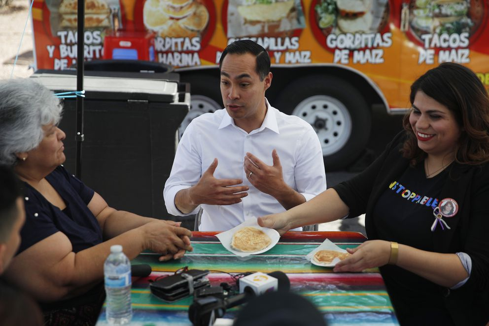 FILE - In this Feb. 28, 2019 file photo former Housing and Urban Development Secretary and Democratic presidential candidate Julian Castro speaks with Lupe Arreola, left, Astrid Silva, right, and others while visiting a taco truck, in North Las Vegas, Nev. As Democrats jockey for support in Nevada, a meeting with Silva, a 31-year-old immigrant rights activist who has become a public face of the 'Dreamers, ' has become a can't-miss early stop. Silva has had dinner with Kamala Harris, policy roundtables with Elizabeth Warren and Joe Biden, and vegan tamales with Cory Booker.(AP Photo/John Locher,File)