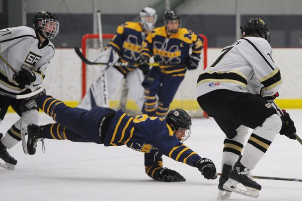 Homer senior forward Ethan Pitzman reaches for the puck during the South Wolverines' 4-2 quarterfinal victory over the Mariners during the state hockey championships at the Menard Center in Wasilla on Thursday, Feb. 13, 2020. (Bill Roth / ADN)