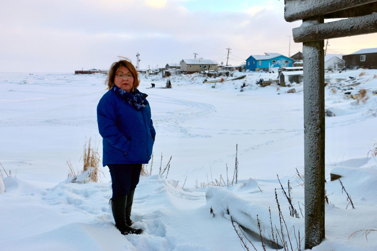 Rosalie Kalistook, general manager of the Chefornak Village Corporation, standing next to her aunt's home just 12 feet from the shoreline on Dec. 16, 2017. (Christine Trudeau / KYUK)