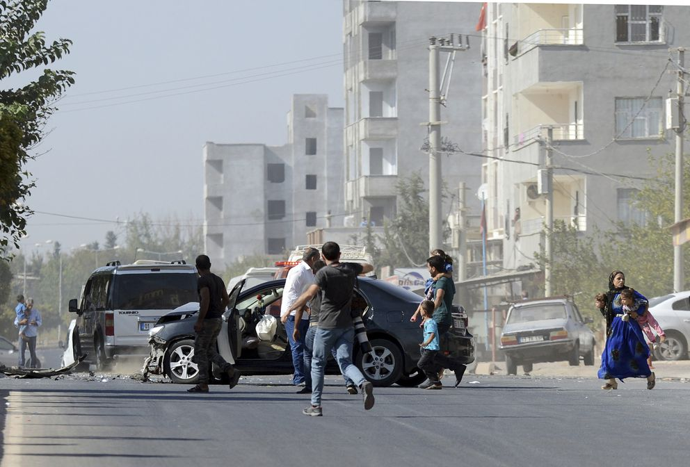 People run to take cover after mortars fired from Syria, in Akcakale, Turkey, Thursday, Oct. 10, 2019. An Associated Press journalist said at least two government buildings were hit by the mortars in Sanliurfa province's border town of Akcakale and at least two people were wounded.( Ismail Coskun/HA via AP )